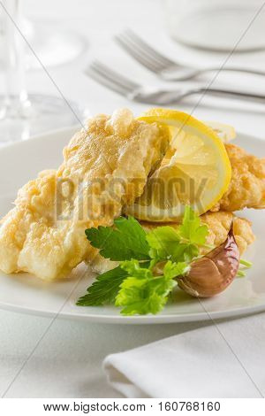 Battered hake fillets with parsley lemon and garlic