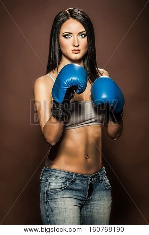 Beautiful brunette woman with blue boxing gloves on brown background