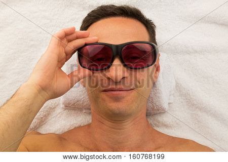 Relaxing man with glasses in spa salon laying on white towel with hand