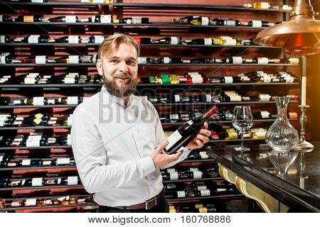 Portrait of a handsome sommelier with wine in front of the shelves with bottles at the luxury supermarket or restaurant