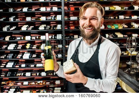 Portrait of a sommelier in uniform with blue cheese and bottle of wine at the restaurant or supermarket. Choosing wine according to the type of cheese. Bottle with empty label to copy paste