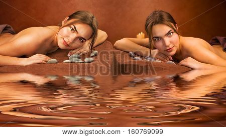 Beautiful lying twins sisters women in a spa salon with water reflection