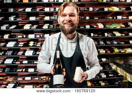 Portrait of a sommelier in uniform with brie cheese and bottle of wine at the restaurant or supermarket. Choosing wine according to the type of cheese. Bottle with empty label to copy paste