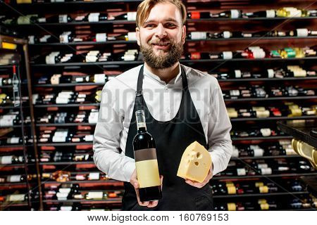Portrait of a sommelier in uniform with gouda cheese and bottle of wine at the restaurant or supermarket. Choosing wine according to the type of cheese. Bottle with empty label to copy paste