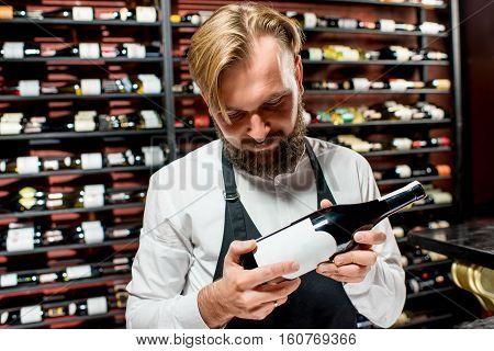 Sommelier choosing wine standing in front of the shelves with wine bottles at the luxury supermarket or restaurant