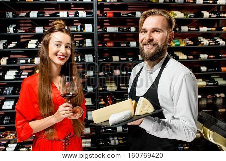 Young woman with glass of wine choosing cheese during the degustation with sommelier or seller at the restaurant or food market