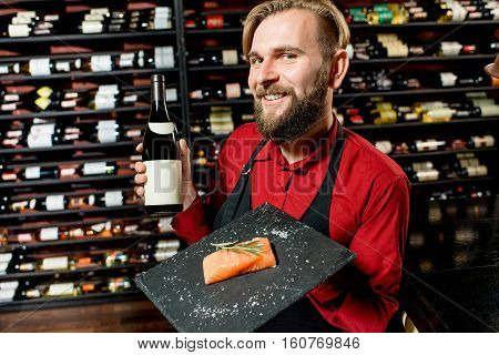 Portrait of a seller or sommelier with wine bottle and salmon on the board at the luxury supermarket or restaurant. Choosing wine according to the type of fish. Bottle with empty label to copy paste
