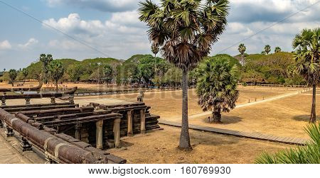 Ancient ruins and pond of Angkor Wat temple, Siem Reap, Cambodia. The statue of Naga serpent cobra king Vasuki in the foreground guards the main road to Angkor Wat which runs tours