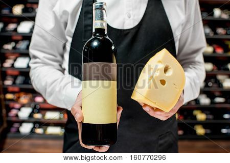 Food seller holding a bottle of white wine and a pieace of gouda cheese. Choosing wine according to the type of cheese. Bottle with empty label to copy paste