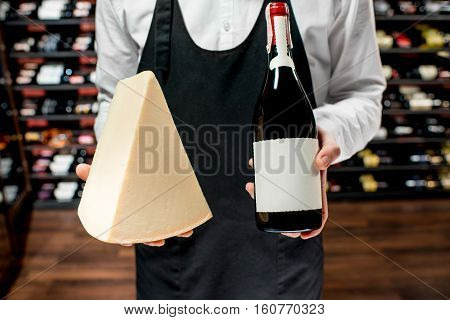 Food seller holding a bottle of white wine and a pieace of parmegiano cheese. Choosing wine according to the type of cheese. Bottle with empty label to copy paste