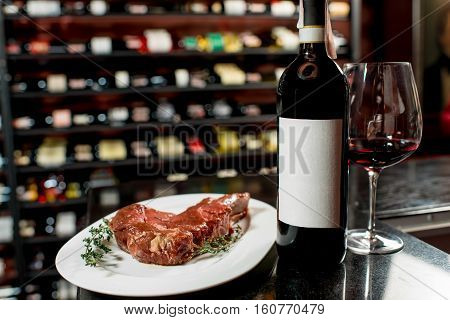 Meat steak with red wine on the table in restaurant or food market. Bottle with empty label to copy paste