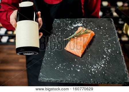 Food seller holding wine bottle and salmon steak at the luxury supermarket or restaurant. Choosing wine according to the type of fish. Bottle with empty label to copy paste