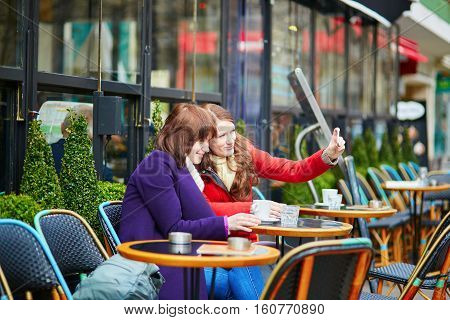 Two Cheerful Girls In A Parisian Street Cafe