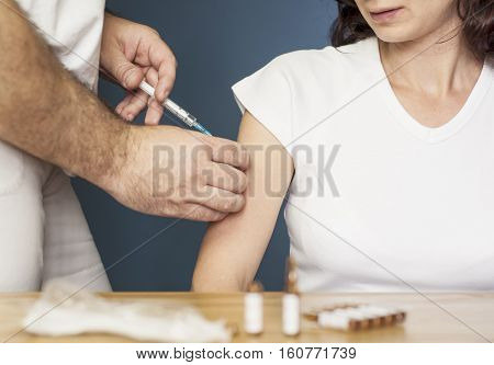 Doctor vaccinating a young woman against flu