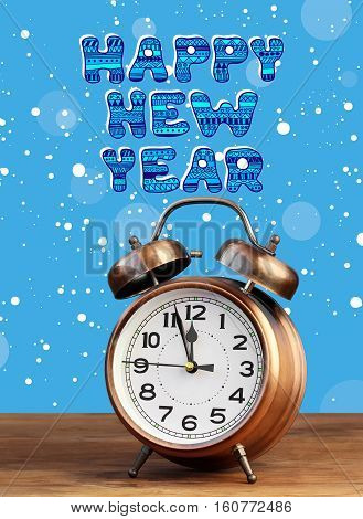 Bronze retro alarm clock at twelve o'clock amid flying snow. Midnight midday. Minutes about New year. happy new year.