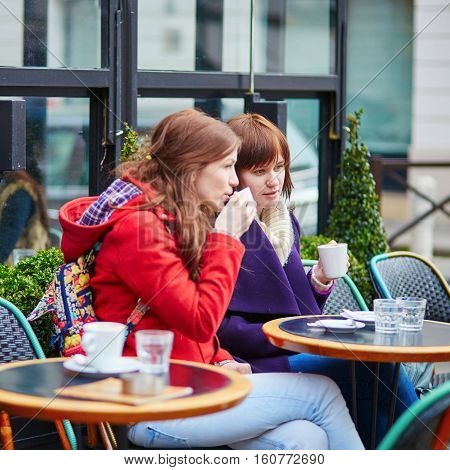 Two Young Girls Chatting In A Parisian Street Cafe