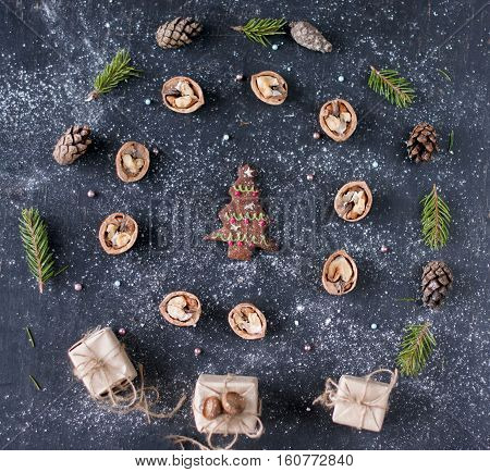 Christmas composition with gingerbread of shape fir tree in the center walnuts pine needles around the cookie. Flat lay