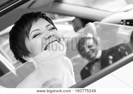 Funny bride in the car smiling groom. Woman 35 years. Wedding.