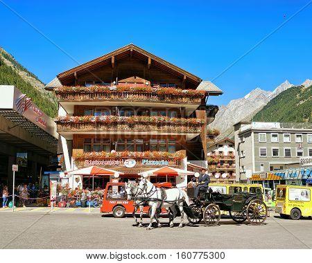 Horse Vehicle And Tourists At City Center Zermatt