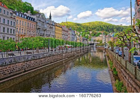 Tepla River embankment and St Mary Magdalene Church in Karlovy Vary the Czech republic. People on the background. poster