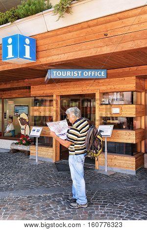 Tourist Looking Into City Map At Tourist Office Of Zermatt