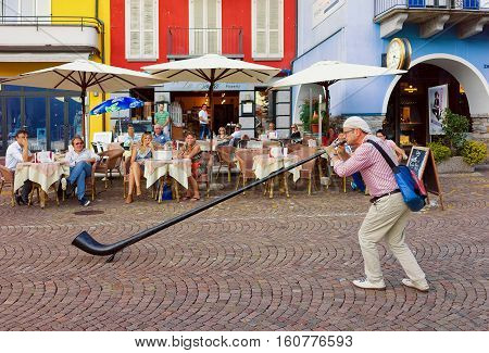 Alphorn Player Entertaining People At Restaurant In Ascona