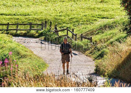 Zermatt Switzerland - August 24 2016: Man doing nordic walking in resort city Zermatt in Switzerland in summer.