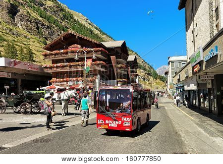 Tourists And Taxi Bus At City Center Of Zermatt