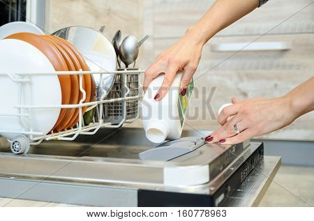 The woman's hand holding a bottle of detergent and adds it in the dishwasher.