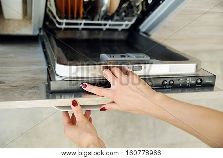 Run the dishwashing machine. Woman's finger pressing the Start button.