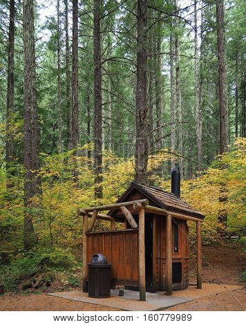 A stylish outhouse in the colorful trees of the woods by the Proxy Falls Trailhead off of the Old McKenzie Highway in Western Oregon on a fall day.