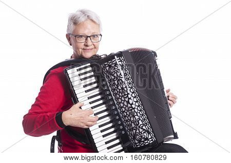elder lady in red with accordion in studio against white background