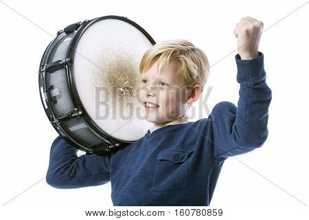 young blond boy with drum against white background in studio shows muscle
