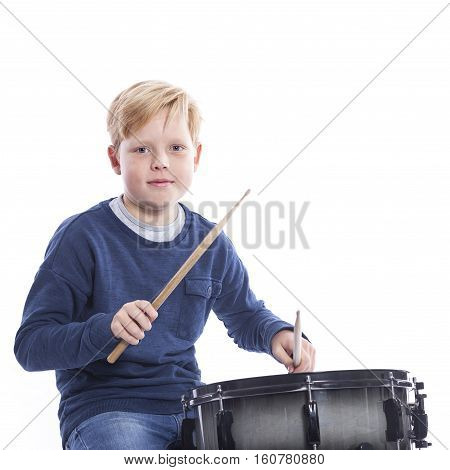 young blond boy plays drum against white background of studio