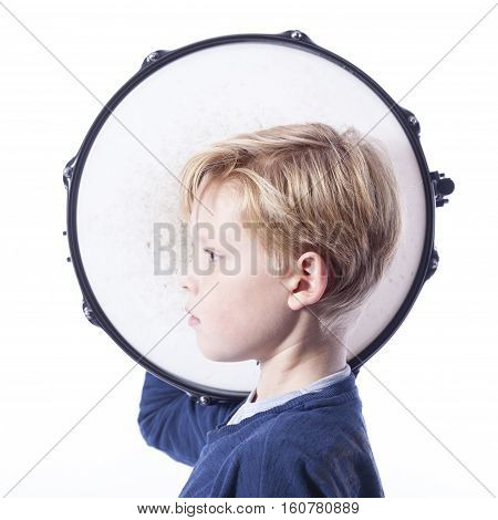 portrait of young blond boy with drum against white background in studio
