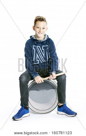 teenage boy sits on drum in studio against white background