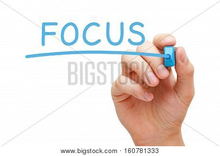 Hand writing Focus with blue marker on transparent wipe board.
