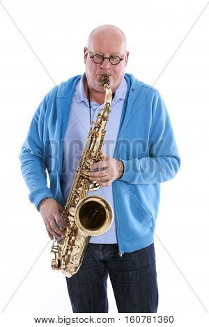 middle aged man in blue plays the tenor saxophone against white studio background