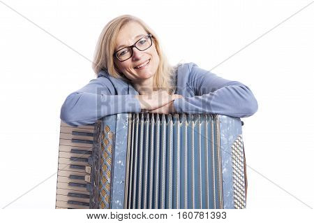 blond woman in blue with glasses leans on accordeon and smiles in studio with white background