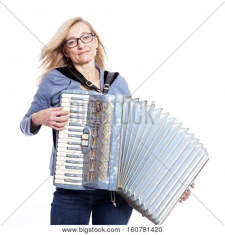 blond woman in blue with glasses plays the accordeon and smiles in studio with white background