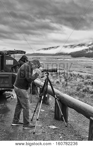 Yellowstone National Park, Wyoming, Usa - October 29, 2016: Wildlife Watcher Observing A Herd Of Wol