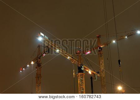 STOCKHOLM SWEDEN - NOV 16 2016: Three yellow cranes in the yellow night light in Hagastaden Stockholm November 16 2016