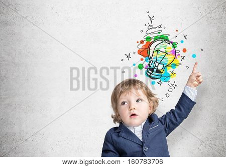 Portrait of an adorable baby boy in a blue suit pointing at a colorful light bulb sketch drawn on a concrete wall. Mock up