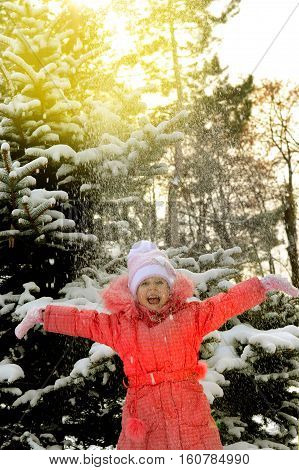 child, kid, (little girl) throws snow up rejoicing.