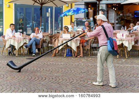 Alphorn Player Entertain People At Restaurant Of Ascona