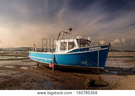 old fishing boat aground at low tide. River Exe. Devon. England