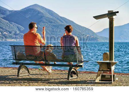 Ascona Switzerland - August 23 2016: Couple eating ice-cream and sitting on the bench at the embankment of the expensive resort in Ascona on Lake Maggiore Ticino canton Switzerland.