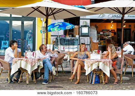 People Relaxing At Street Restaurant In Ascona Town In Swiss