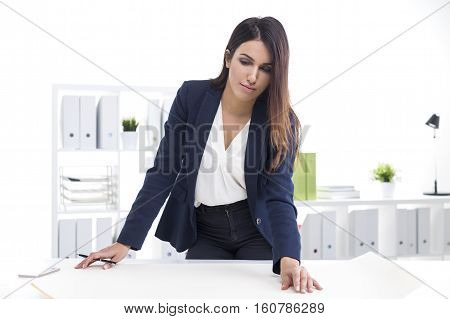 Portrait of a serious woman architect working with blueprints in her office. She is standing near her table and looking at them