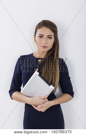 Portrait of a serious young businesswoman in a black dress holding her tablet and looking at the viewer